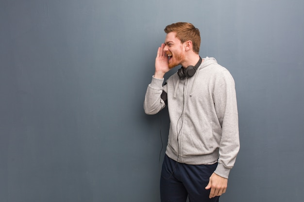 Homme rousse jeune fitness chuchotant une rumeur potins