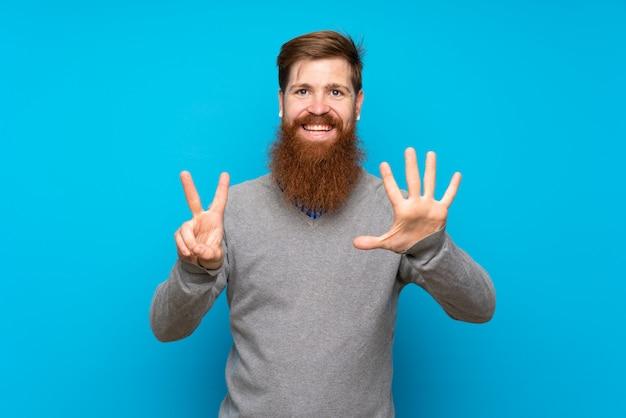 Homme rousse avec longue barbe sur bleu isolé comptant sept avec les doigts