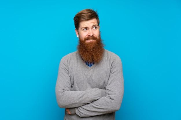 Homme rousse à longue barbe sur bleu isolé avec une expression de visage confuse