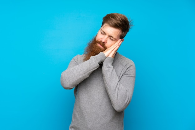 Homme rousse avec longue barbe sur bleu isolé faisant un geste de sommeil dans une expression dorable
