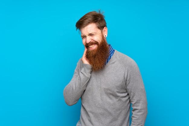 Homme rousse à longue barbe sur bleu isolé avec maux de dents