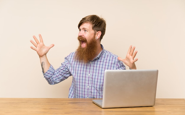 Homme rousse avec une longue barbe dans une table avec un ordinateur portable avec une expression faciale surprise