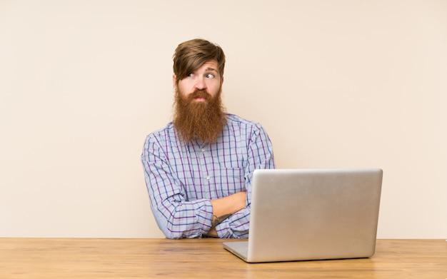 Homme rousse avec une longue barbe dans une table avec un ordinateur portable, pensant à une idée