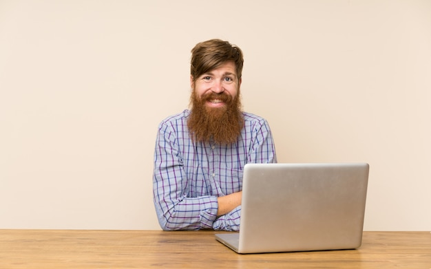 Homme rousse avec une longue barbe dans une table avec un ordinateur portable en riant