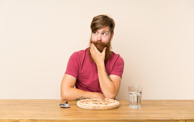 Homme rousse à la longue barbe dans une table et avec une pizza qui pense à une idée