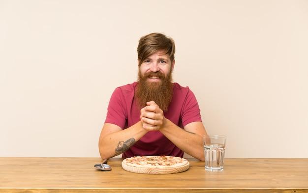 Homme rousse avec une longue barbe dans une table et avec une pizza souriant beaucoup