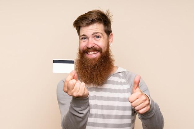 Homme rousse avec une longue barbe détenant une carte de crédit