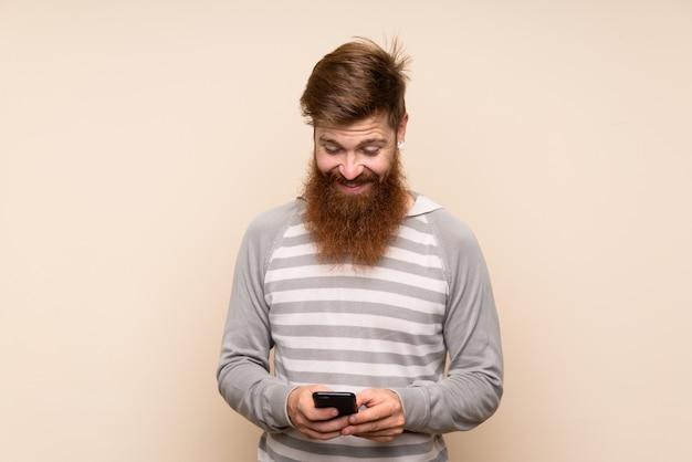 Homme rousse à la longue barbe envoyant un message