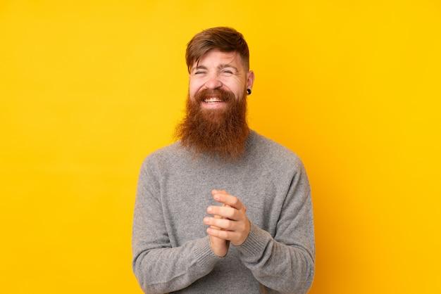 Homme rousse à longue barbe sur jaune isolé applaudissant après présentation lors d'une conférence