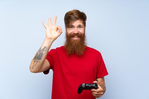 Homme rousse avec une longue barbe jouant avec un contrôleur de jeu vidéo montrant un signe ok avec les doigts