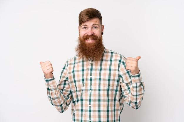 Homme rousse avec une longue barbe sur un mur blanc isolé avec le geste du pouce en l'air et souriant