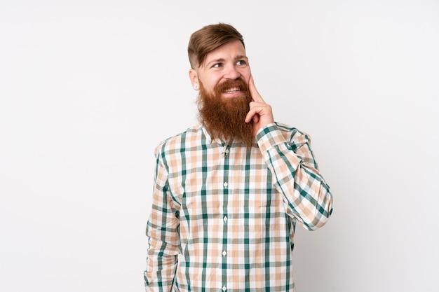 Homme rousse avec une longue barbe sur un mur blanc isolé en pensant à une idée tout en regardant