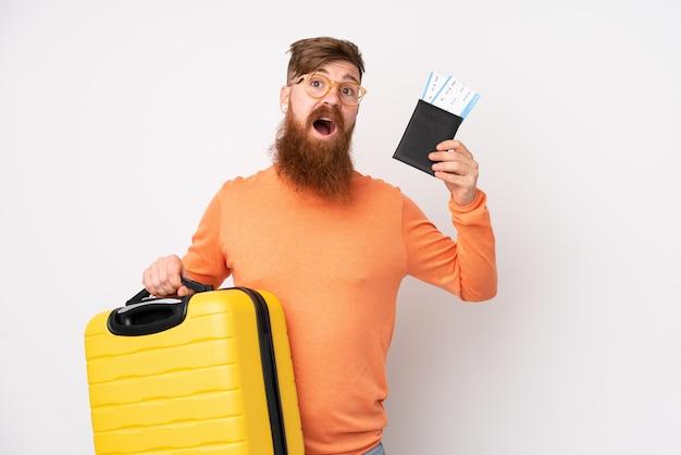 Homme rousse avec une longue barbe sur un mur blanc isolé en vacances avec valise et passeport