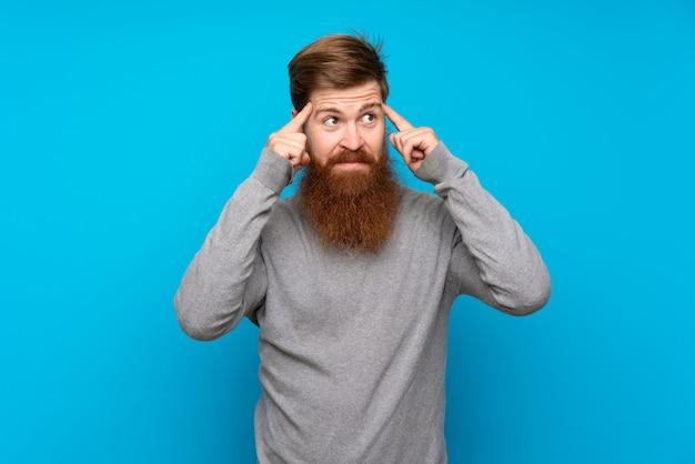 Homme rousse avec longue barbe sur mur bleu ayant des doutes et de la pensée