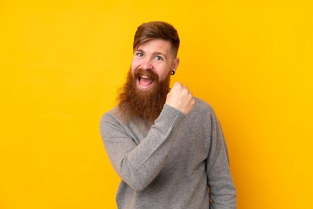 Homme rousse avec longue barbe sur mur jaune isolé célébrant une victoire