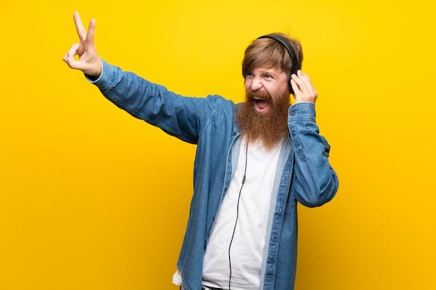 Homme rousse avec une longue barbe sur un mur jaune isolé, écouter de la musique avec des écouteurs