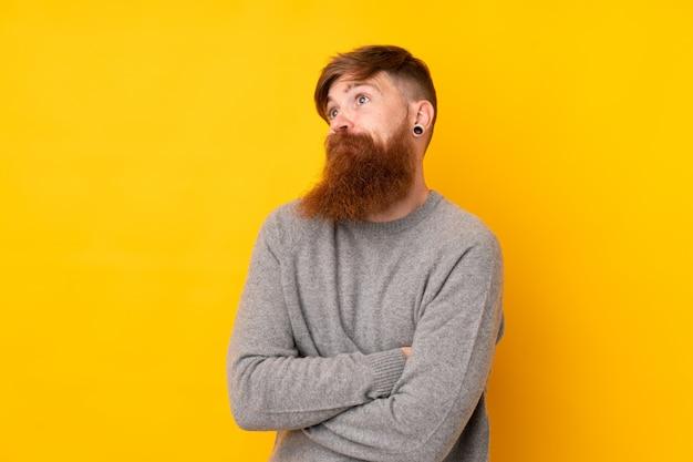 Homme rousse avec une longue barbe sur un mur jaune isolé faisant un geste de doute tout en soulevant les épaules