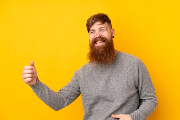 Homme rousse avec une longue barbe sur un mur jaune isolé faisant un geste de guitare
