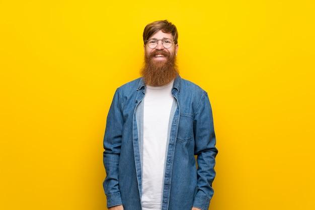 Homme rousse avec une longue barbe sur un mur jaune isolé avec des lunettes
