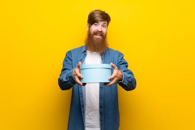Homme rousse avec une longue barbe sur un mur jaune isolé, tenant une boîte-cadeau