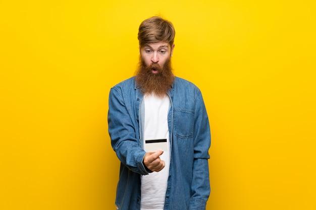 Homme rousse avec une longue barbe sur un mur jaune isolé, tenant une carte de crédit