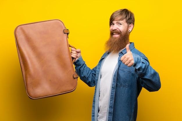 Homme rousse avec une longue barbe sur un mur jaune isolé, tenant une mallette vintage