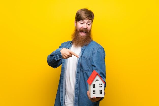 Homme rousse avec une longue barbe sur un mur jaune isolé tenant une petite maison