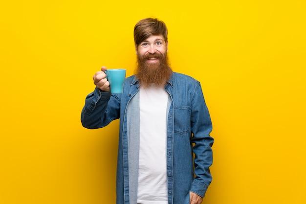 Homme rousse avec une longue barbe sur mur jaune isolé, tenant une tasse de café
