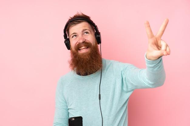 Homme rousse avec une longue barbe sur le mur rose isolé écouter de la musique et chanter