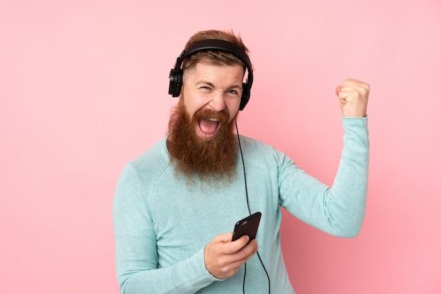 Homme rousse avec longue barbe sur mur rose isolé écouter de la musique et faire un geste de guitare