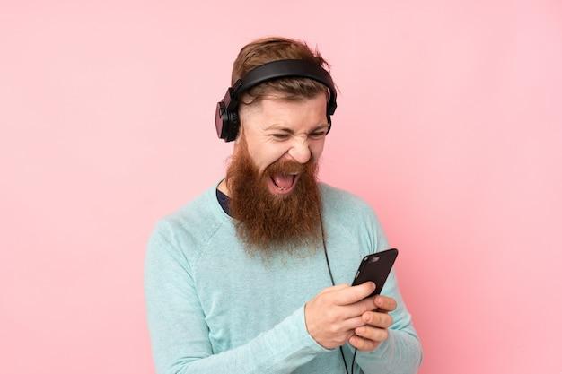 Homme rousse avec longue barbe sur mur rose isolé écouter de la musique avec un mobile et chanter