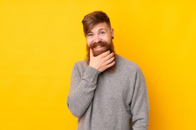 Homme rousse avec longue barbe sur la pensée de mur jaune isolé