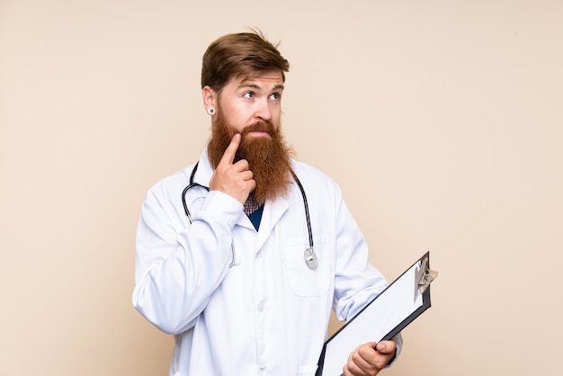 Homme rousse avec une longue barbe avec une robe de docteur et tenant un dossier en pensant