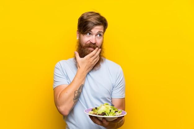 Homme rousse avec une longue barbe et salade sur un mur jaune isolé, pensant à une idée