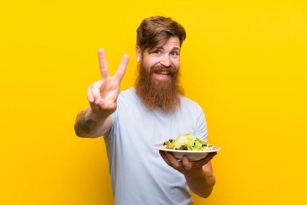 Homme rousse avec une longue barbe et salade sur un mur jaune isolé, souriant et montrant le signe de la victoire