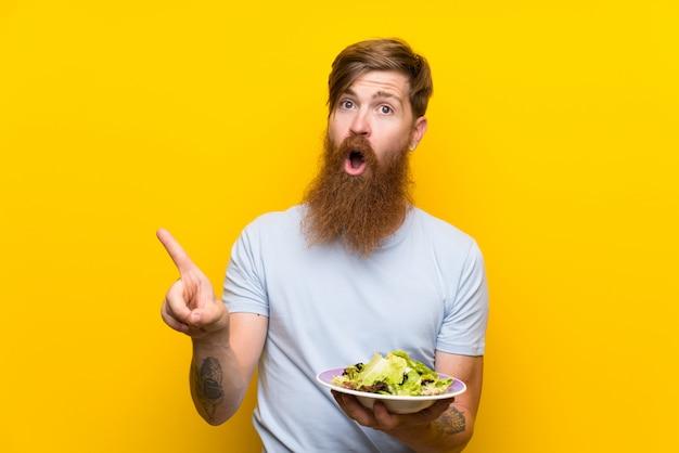 Homme rousse avec une longue barbe et salade sur un mur jaune isolé surpris et pointant le côté