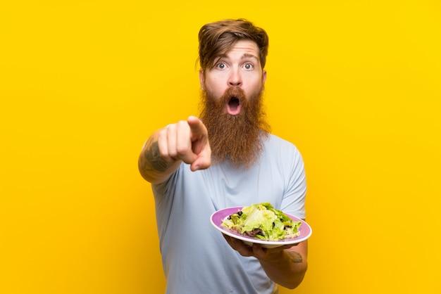 Homme rousse avec une longue barbe et salade sur un mur jaune isolé surpris et pointant le devant