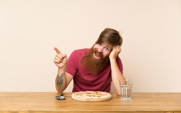Homme rousse avec une longue barbe sur une table et une pizza surprise et pointant du doigt sur le côté