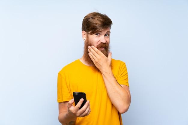 Homme rousse avec une longue barbe avec un téléphone portable sur un mur bleu, pensant à une idée