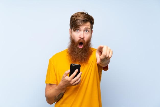 Homme rousse avec une longue barbe avec un téléphone portable sur le mur bleu surpris et pointant le devant