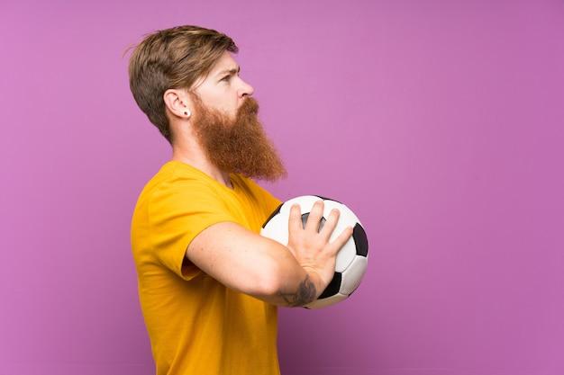 Homme rousse avec une longue barbe tenant un ballon de foot sur un mur violet isolé