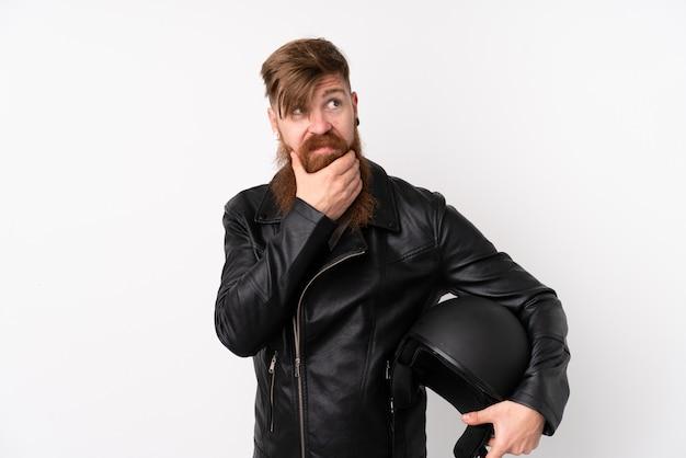 Homme rousse à longue barbe tenant un casque de moto sur un mur blanc isolé en pensant à une idée