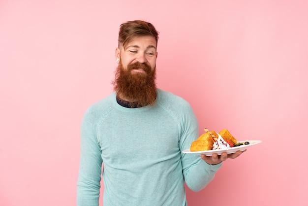 Homme rousse avec une longue barbe tenant des gaufres sur un mur rose isolé avec une expression heureuse