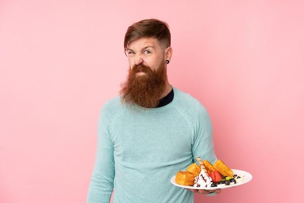 Homme rousse avec une longue barbe tenant des gaufres sur un mur rose isolé faisant un geste de doute tout en soulevant les épaules