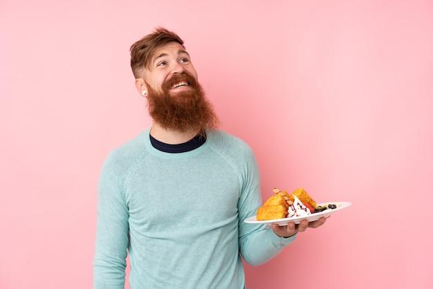 Homme rousse avec longue barbe tenant des gaufres sur un mur rose isolé en levant tout en souriant