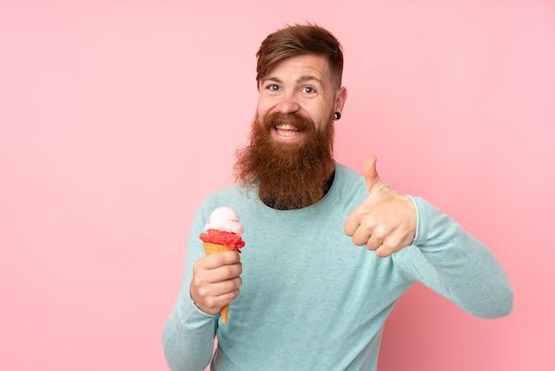 Homme rousse à longue barbe tenant une glace au cornet sur un mur rose isolé avec les pouces vers le haut parce que quelque chose de bien s'est produit