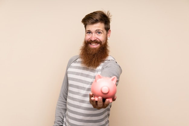 Homme rousse avec une longue barbe tenant une grande tirelire