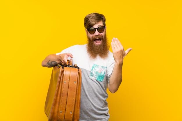 Homme rousse avec une longue barbe tenant une mallette vintage invitant à venir avec la main. heureux que tu sois venu