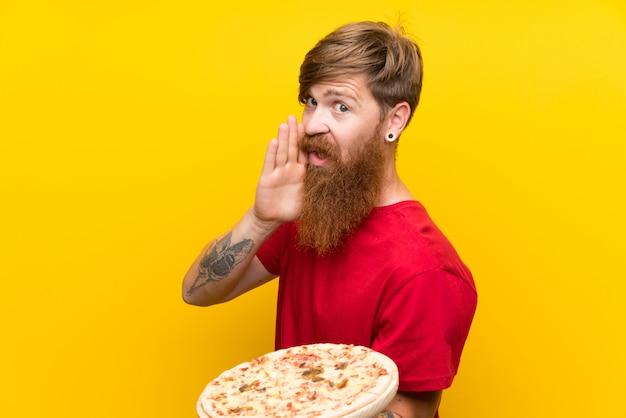 Homme rousse avec une longue barbe tenant une pizza sur un mur jaune isolé chuchotant quelque chose