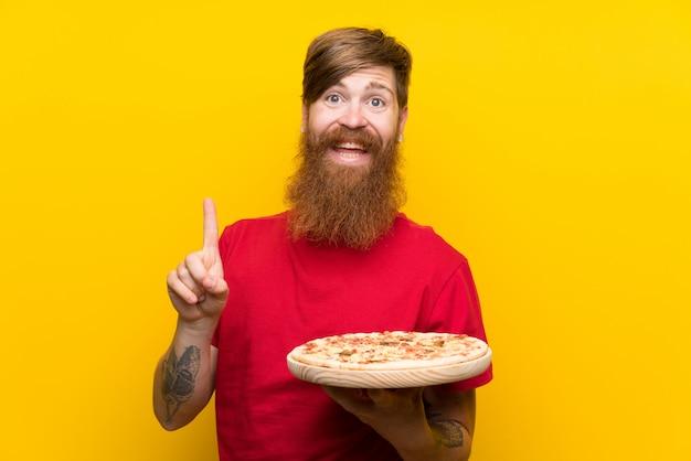 Homme rousse avec une longue barbe tenant une pizza sur un mur jaune pointant vers le haut une excellente idée